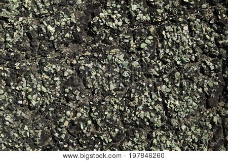 Roofing green stones in black resin texture close-up