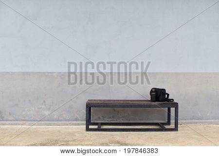 lens and camera bag on steel long bench in front of dirty gray old wall for waiting to work in working day