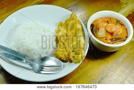 fried egg  on rice eat couple with spicy prawn Tom Yum soup