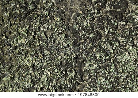 Roofing a lot of green pebbles in black resin texture close-up