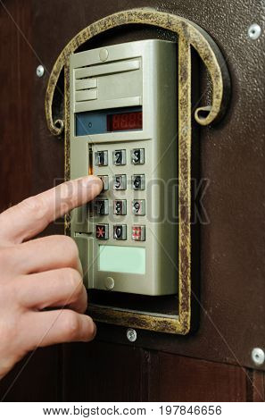 Man's hand is dialing the code on the door intercom of the front door.