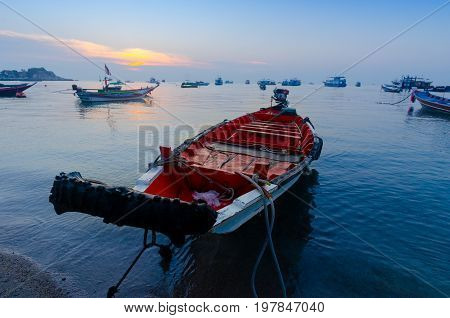 A boat with an old tyre bumper is anchored next to the shore in Ko Tao's natural bay in Thailand.