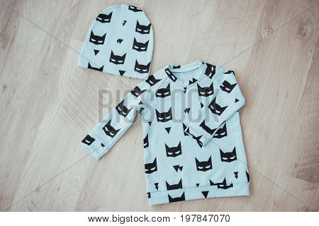 Children's tracksuit on light wooden background. Children's tracksuitbaby products