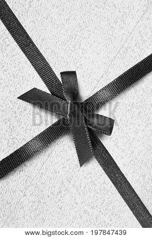 Black silk ribbon tied on white wrapping paper