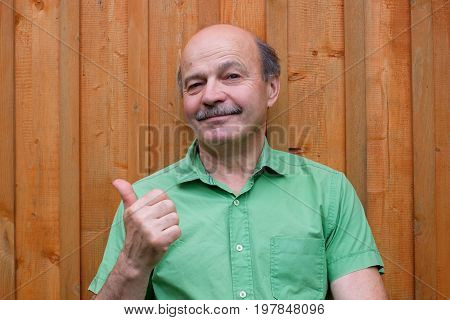 Caucasian mature man with thumbs up gesture on wooden background