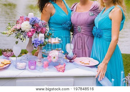 Bridesmaids are hugging near the festive table at the ceremony. Wedding decoration in the style of boho floral arrangement decorated table in the garden. Close-up