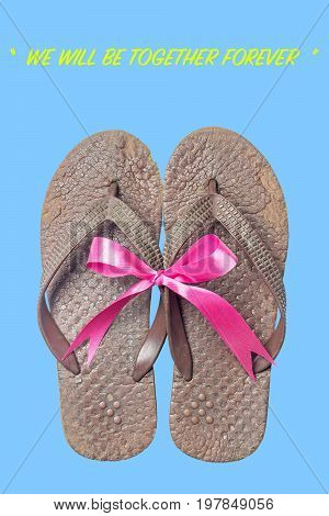 Old sandals on isolate blue background. Brown slippers with pink bow. Concepcion is we will be together forever.