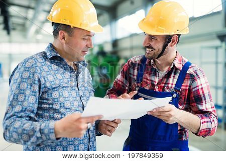 Supervisor and engineer working in metal industry factory