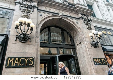 New York July 27 2017: Woman is passing by an entrance to the Macy's department store in Manhattan.