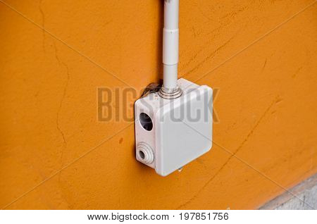 electrical box for splicing out door, on yellow wall .