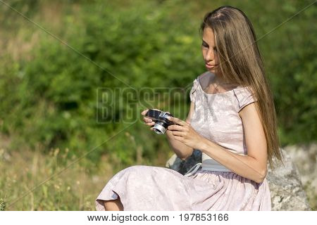 Beautiful woman is holding old fashioned camera in hand, outdoors. Stock photo