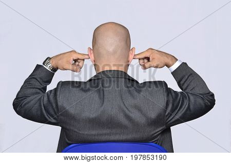 Back view from a bald head businessman covering his ears with fingers.