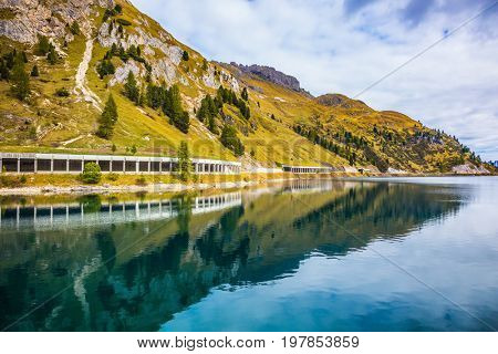 Mountain Lake Lago di Fedaia, Dolomites. The concept of ecological tourism. Glacial lake with clear cold water. The harmony of the Dolomites