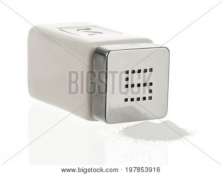 Salt spilling from glass salt shaker isolated on white background.