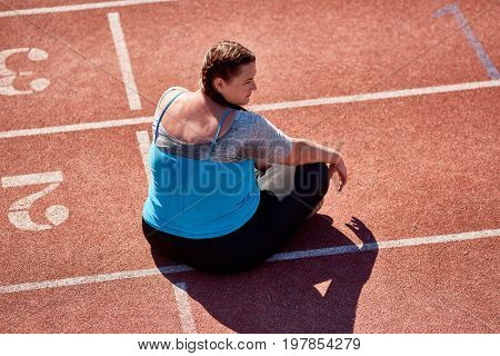 Sweaty and plump young active female sitting on race track on sunny day
