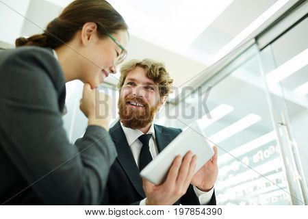 Portrait of enthusiastic bearded businessman showing data at digital tablet  to colleague discussing project in office