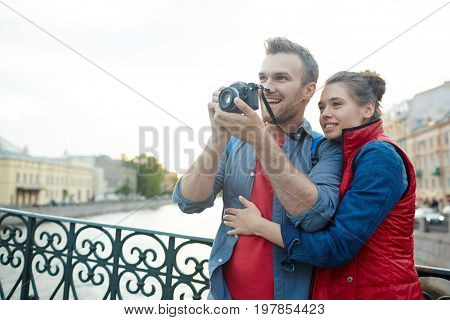 Young man with photocamera photographing sights of the city he and his girlfriend visit