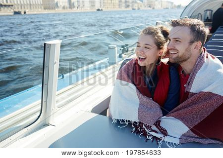 Cheerful couple wrapped in plaid sightseeing on voyage