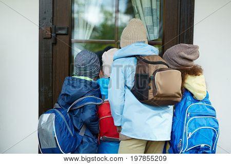 Curious schoolkids with rucksacks looking through school door