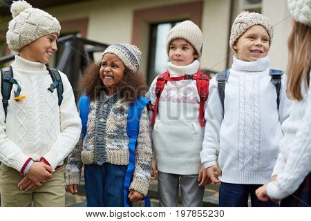 Kids in knitwear talking outdoors at the end of school day