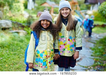 Two affectionate junior school learners in campus