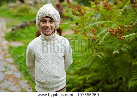 Happy youngster in knitwear spending leisure in park