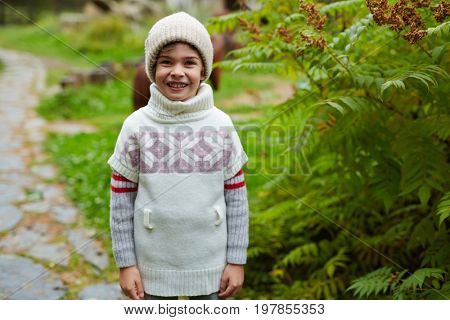 Little schoolboy in beanie and sweater in natural environment