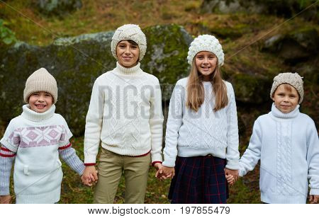 Friendly kids in knitted casualwear holding by hands