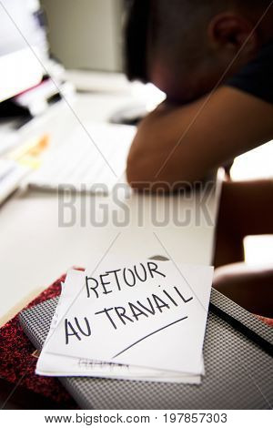 closeup of a concerned man sitting at his office desk and a note in the foreground with the text retour au travail, back to work written in french