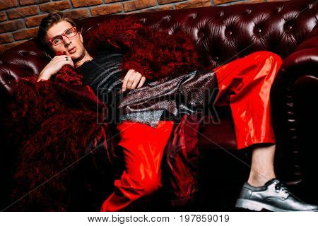 Vogue shot. Imposing fashion male model posing in long red fur coat and designer clothing. Men's beauty, fashion. Luxurious apartments.