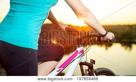 Young Woman Resting with Mountain Bike on the Summer Rocky Trail at Sunset. Closeup of Hands with Smart Watch on the Handlebar. Training and Sports Concept.