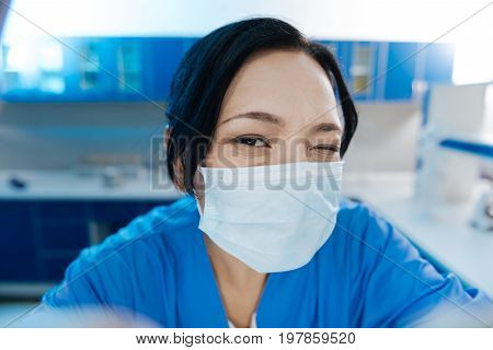 Everything will be great. Happy positive delighted surgeon smiling and winking at you while being in a good mood