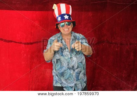 A man poses for photos in a Photo Booth. A man wears an American Flag Hat and points and smiles to the camera in a Photo Booth.