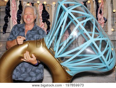 A man poses for photos in a Photo Booth. A man holds a Giant Wedding Ring and smiles while in a Photo Booth.
