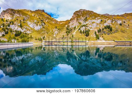 Mountain Lake Lago di Fedadia, Dolomites. Glacial lake with clear cold water. Cool autumn day at Mount Marmolada. The concept of ecological and extreme tourism