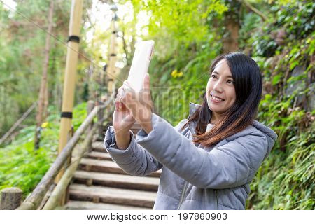 Woman taking photon in the hiking trail