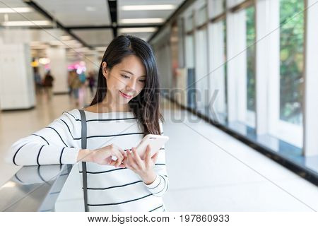 Woman use of mobile phone in the station