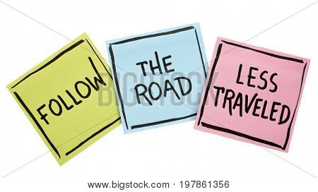 Follow the road less traveled advice or reminder - handwriting in black ink on isolated sticky notes