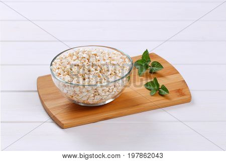 bowl of puffed buckwheat on wooden cutting board