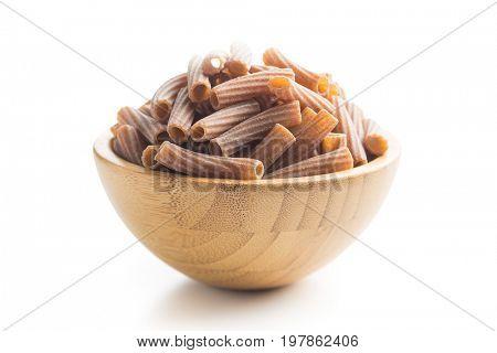 Dried rigatoni pasta in wooden bowl isolated on white background. Dark semolina pasta.