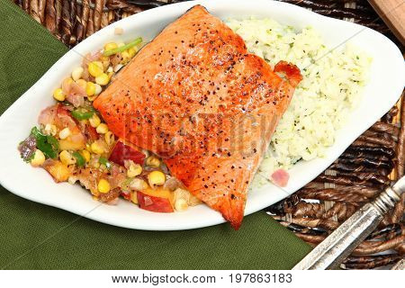 Pan fried salmon fillet with peach and corn salsa and lime and cilantro jasmine rice.