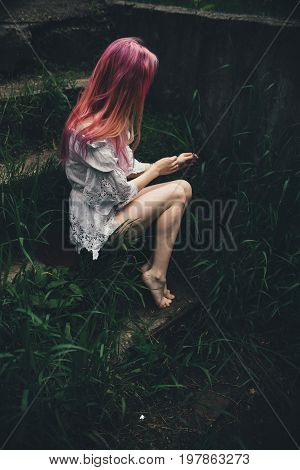 The beautiful girl with pink hair sits on the thrown ladder in an environment of a green grass in the summer