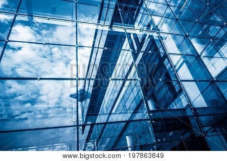 modern glass building with reflection,blue toned.