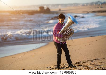 Young man play Tuba musical instrument on sea shore outdoor.