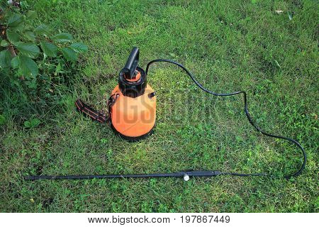 Garden plastic hand pump sprayer with boom on grass. Top view.