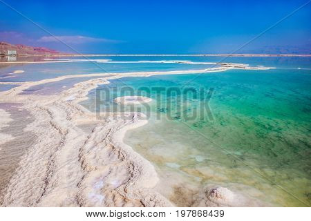 Very salty water glows with turquoise light. Reduced water in the Dead Sea. The concept of ecological and medical tourism. The evaporated salt has developed into fantastic patterns