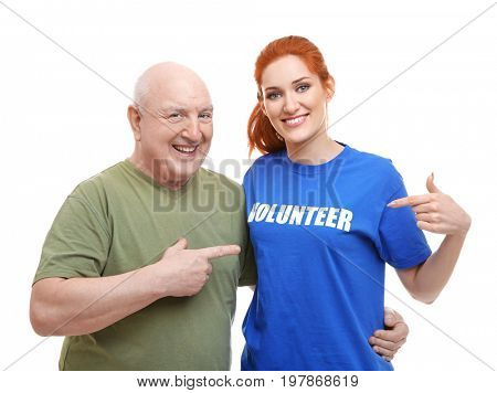 Young woman and senior man pointing at t-shirt with text VOLUNTEER, on white background