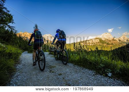 Mountain biking couple with bikes on track at sunset, Cortina d'Ampezzo, Dolomites, Italy