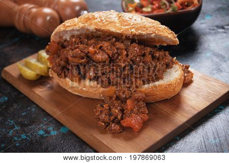 Ground beef sandwich served on wooden board
