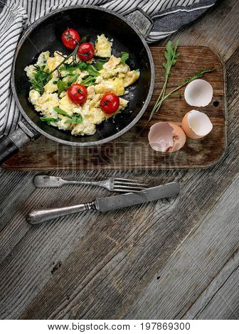 Omelette with ripe tomatoes in rustic pan, topview